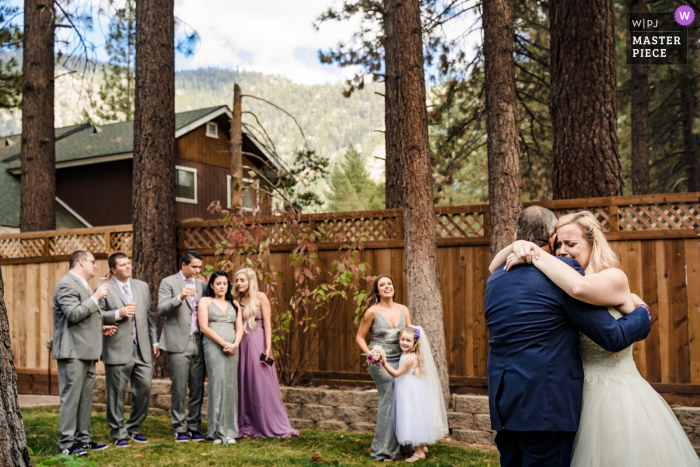 Wedding photo from California - Emotional father-daughter dance as the bridal party parties around them