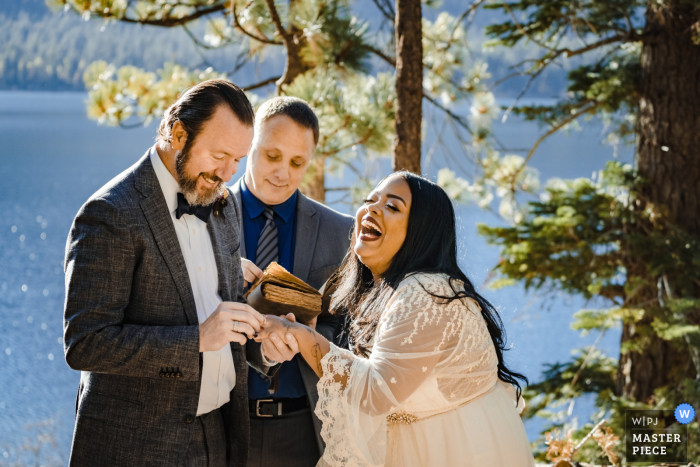 Wedding photo from California - Bride laughs with glee as her husband puts on her wedding ring.