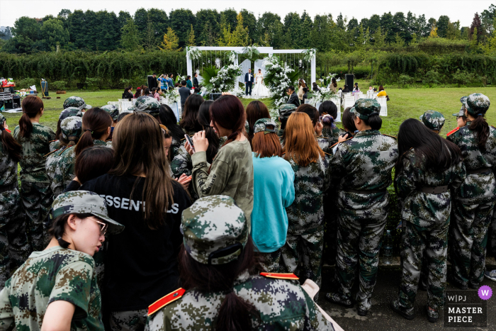 Wedding photo from China - The newlyweds are having a wedding ceremony. A group of military training students nearby are watching the wedding ceremony.