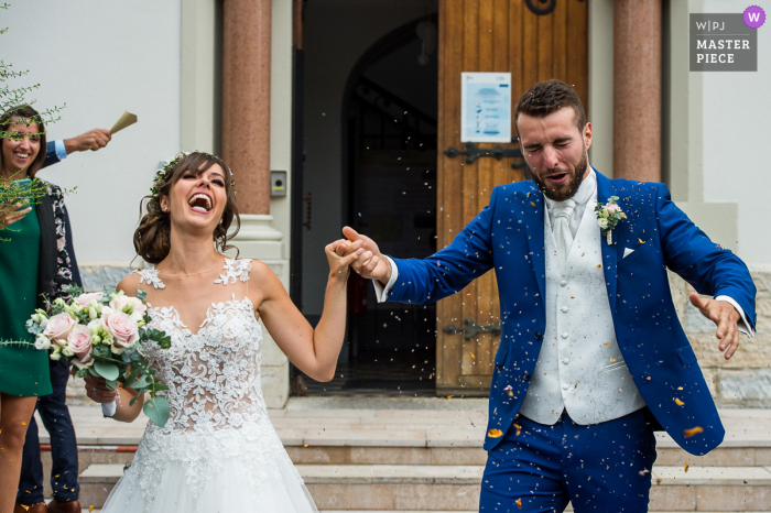 Wedding photography from the steps of the City hall of Chapareillan, France with the Bride and groom under a rain of confetti at the end of the civil ceremony