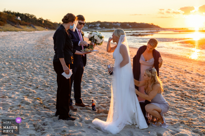 Massachusetts beach wedding photo from Brewster MA of the Bridesmaids as they bustle the bride's dress