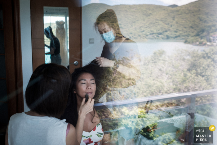 Wedding photography from Wong Keng Tei, Sai Kung, Hong Kong (Bride's home) - Bride having her make-up done, the natural surroundings of her house and her wedding gown were reflected by the glass door of there terrace.