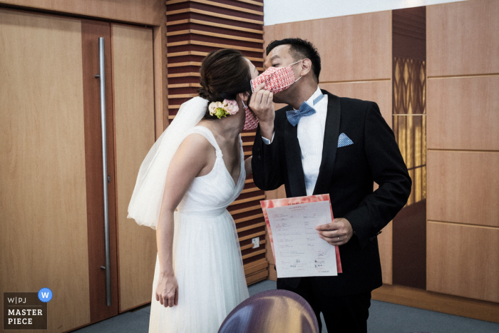 Wedding photography from City Hall Marriage Registry, Hong Kong of The groom taking off the face mask and kiss the bride, upon the completion of the ceremony