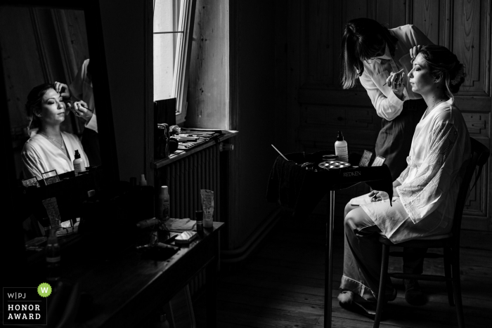French black and white wedding photo from Auvergne-Rhône-Alpes of the bride who gets made up with her reflection in the mirror