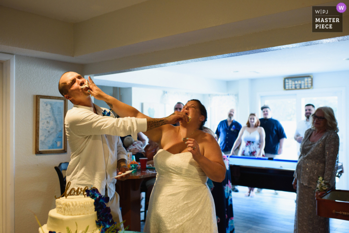 North Carolina wedding reception photo from Corolla of the Bride and groom smashing cake in each other's faces