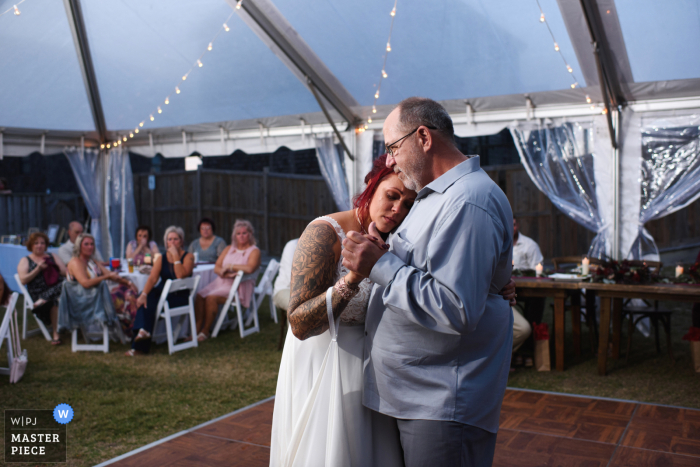 North Carolina wedding photo from South Nags Head showing the Bride is emotional as she dances with her father