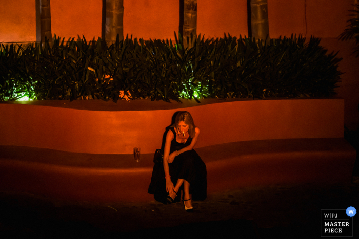 MX wedding photography from casa hyder, san miguel de allende, mexico as A wedding guest takes a break during the dancing portion of the reception