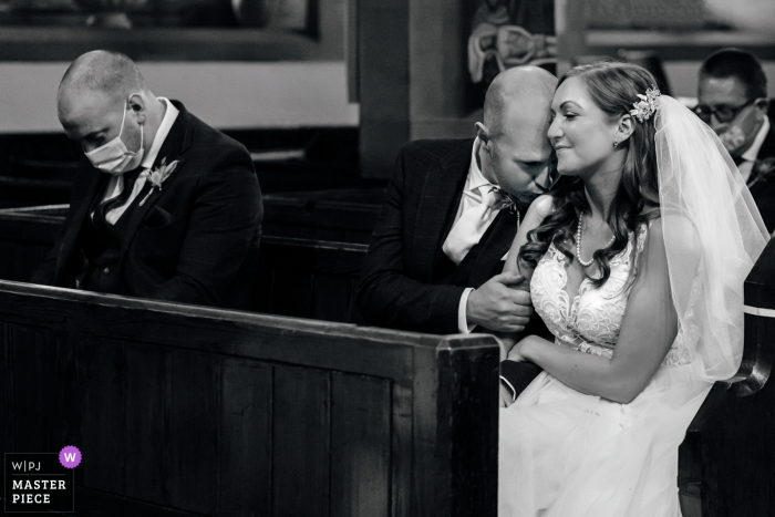 Lancashire wedding reportage photography from Clitheroe showing A gentle kiss during a covid ceremony