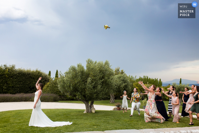 Auvergne-Rhône-Alpes outdoor wedding image of the bridal bouquet toss on the grass