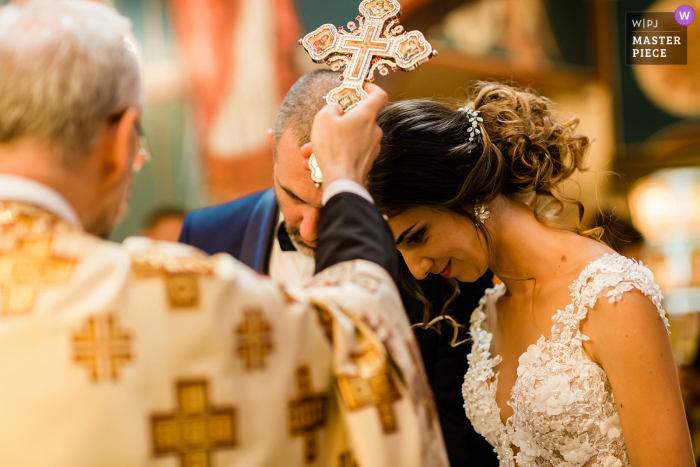 "Bulgaria wedding photography from Church ""Vyzdvizhenie na svetiya kryst gospoden"" in Sofia	as The father places the cross on the heads of the newlyweds"