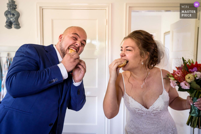 "A Netherlands bride and groom are eating a ""worstenbroodje/meat sandwich"" A typical Dutch wedding tradition in the state of Brabant"