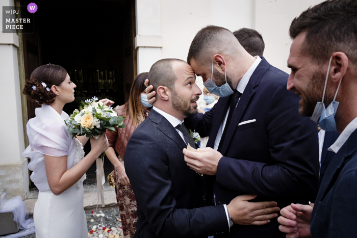 Italian wedding image of the Groom greeting a friend after the ceremony at Chiesa di San Giulio in Vizzola Ticino