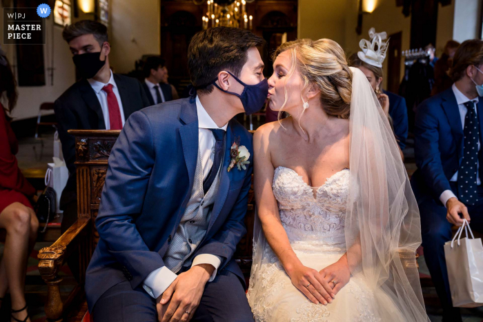 City Hall in Haarlem wedding photo capturing a moment after the ceremony where the groom has his facemask ready. The bride is giving him a kiss