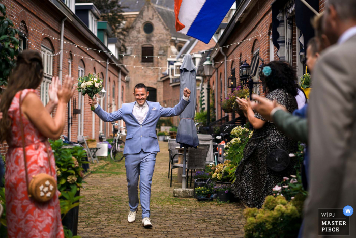 Naaldwijk The Netherlands wedding photo of the groom walking down the alley to see his bride. He is excited
