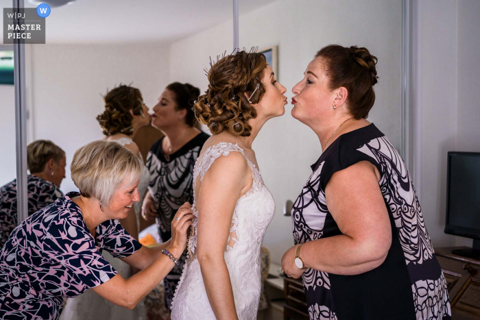 Netherlands wedding preparation image of the bride getting ready and her mother is giving her a loving kiss
