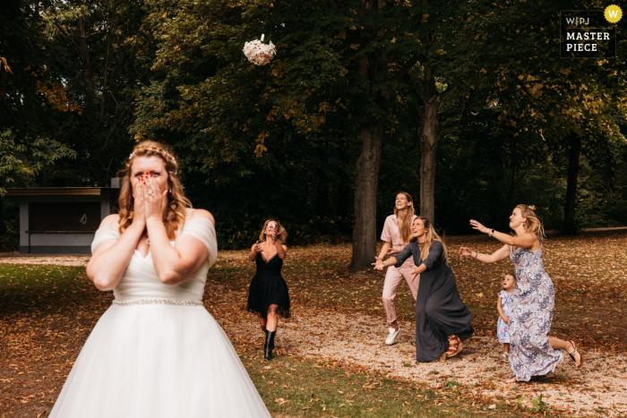 Antwerpen outdoor wedding pic of the bride tossing her bouquet
