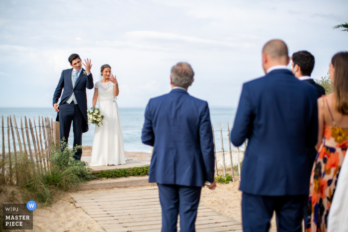 Les Portes-en-Ré beach wedding photograph of the bride and groom showing off their rings to the guests after the ceremony