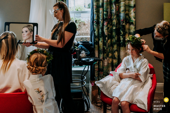 Harrogate, North Yorkshire, UK wedding image of the bride getting ready in the morning, with the daughter looking towards her mum (the bride) as she admires herself in the mirror