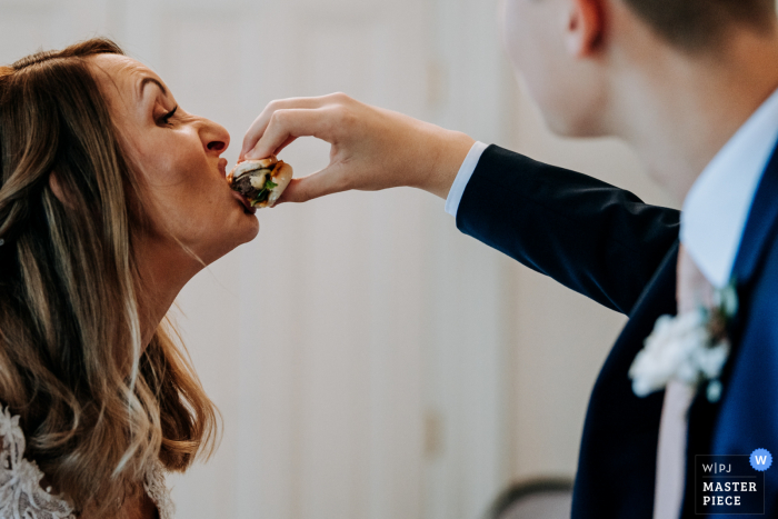 Dunedin, Hull wedding image of the bride being fed a burger by her step son so she doesn't get any food on her dress in East Yorkshire