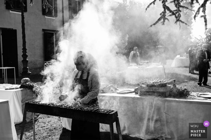 Villa Caproni, Vizzola Ticino, Italy wedding photography of a smoke-filled frame as the cook barbecues at the grill