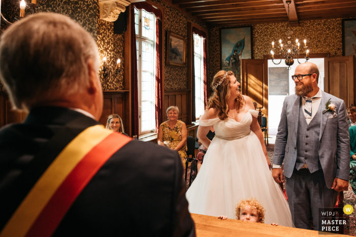 Flanders wedding photography at a town hall of the bride and groom's son is watching the minister closely from under the table during the ceremony