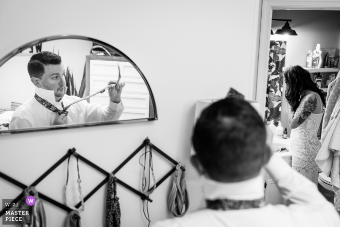 Wedding photograph of the groom working on tying his tie while his bride puts on her earrings in their bathroom. They were getting ready together in preparation to head out into the mountains for their elopement with just the two of them and an officiant.