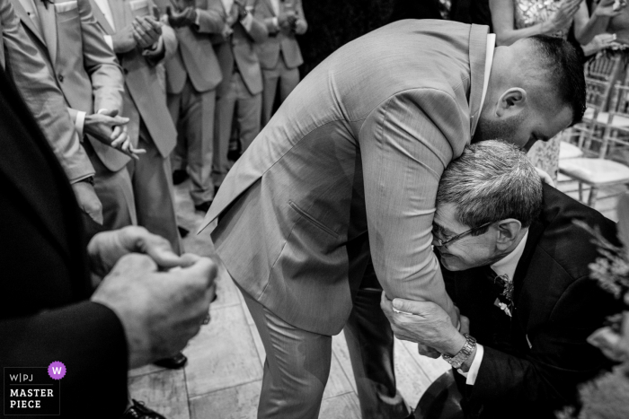 Pennsylvania wedding photo of the bride's father, who is suffering severely from multiple sclerosis, gives her away by pulling the groom in and whispered something to him that will forever stay between them