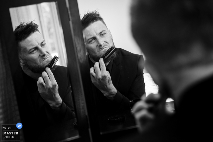 Pennsylvania wedding photography of the Groom combing out his beard in final preparations for the ceremony