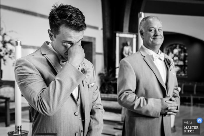 Pennsylvania wedding photo of the groom's reaction to seeing his bride walk into the church as his father/best man takes it all in.