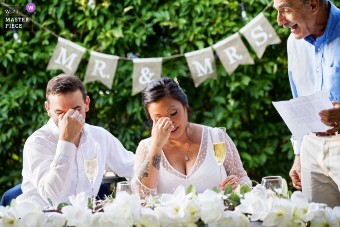 Wedding photograph from New Jersey - bride and groom make same reaction as bride's dad toasts during NJ backyard wedding
