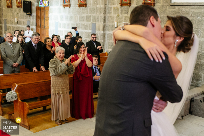 Wedding photography from Igreja Matriz de Gramado of the bride and groom kissing during the indoor ceremony