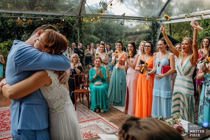 Wedding photo from Rio Grande do Sul of the bride and groom hugging under a clear tent ceremony