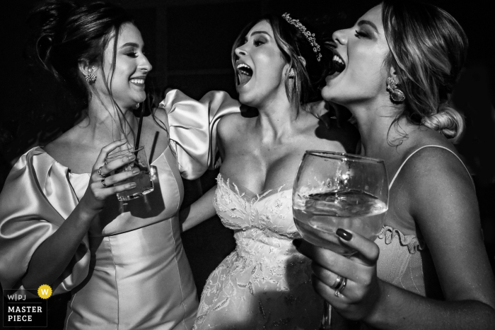 Villa Borguese Anápolis wedding image of the bride with two friends singing in this black and white reception pic