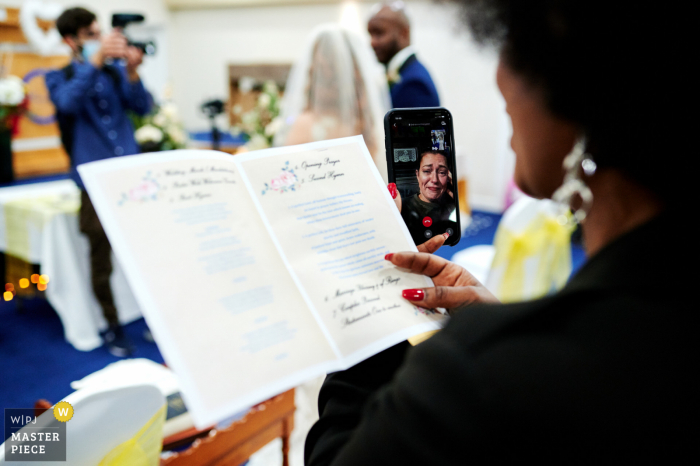 Church in Croydon, UK wedding photo displaying an emotional long distance guest watching the live stream of the wedding ceremony