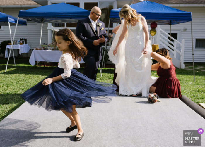 Schenectady, NY wedding photographer captured a little flower girl spinning in her dress while behind her the bride's dress is being bustled by her bridesmaids and her new husband stands by