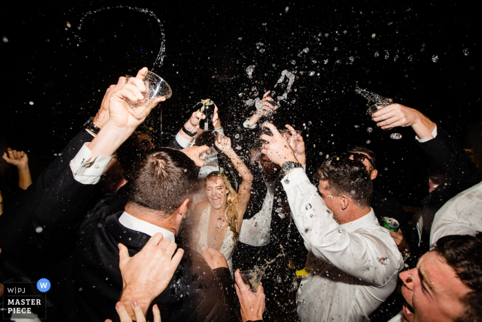 Big Sky, Montana wedding image of the bride and guests partying with drinks spraying above their heads