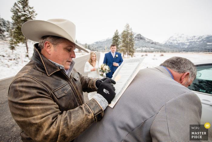 Yellowstone wedding image of the father of bride using the father of groom's back to fill out marriage certificate