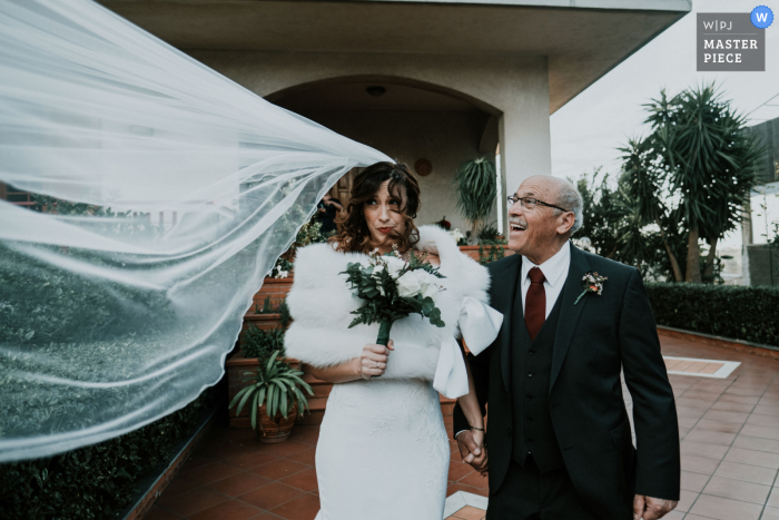Rome, Italy wedding photo showing Too much wind this day - the dad is enjoying this so much