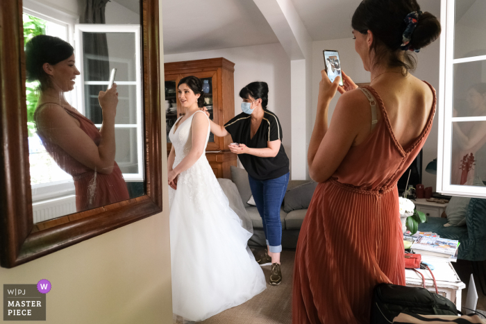 Limoges wedding photography with the Bride getting ready and people helping and taking pictures