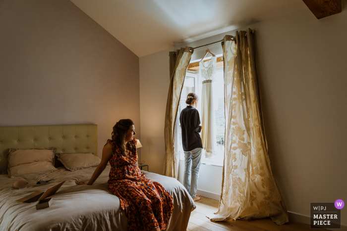 Auvergne-Rhône-Alpes Reception wedding photography created as The bride waits to get ready, she looks out the window to try to see her future husband