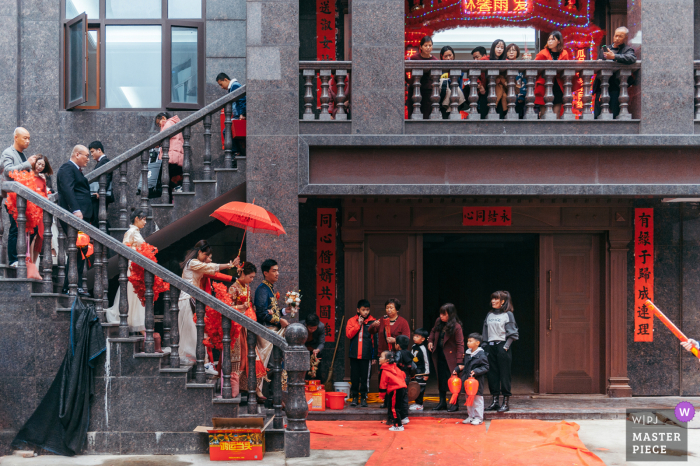 Fujian home wedding photography of the full bridal party coming down the stairs with a red umbrella