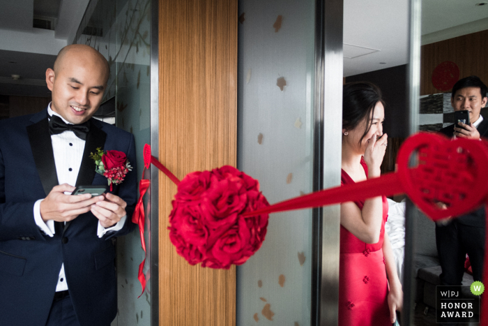 HK wedding photo from Hotel Icon, Hong Kong of the Bride, hiding at the room, reacts as the groom reads out the 'declaration of love', before meeting the bride for the first time. The bride's brother is watching on and filming with his phone, as reflected