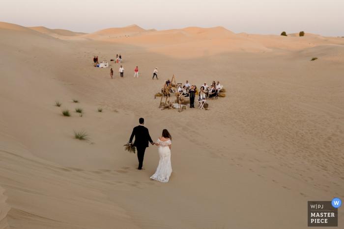 Dubai Desert wedding photography of the couple walking the sands on Returning to the desert reception