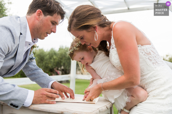 Cérémonie Laïque wedding photo of the Finger Signing of the marriage certificate for a child