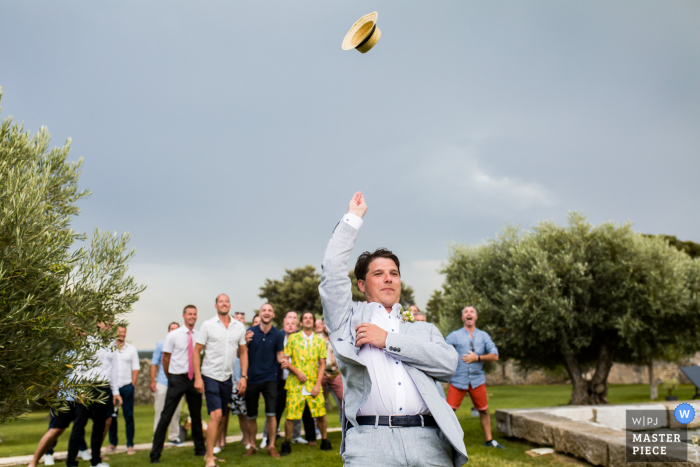 Vin d'honneur wedding photography of the groom tossing his hat to the men outdoors