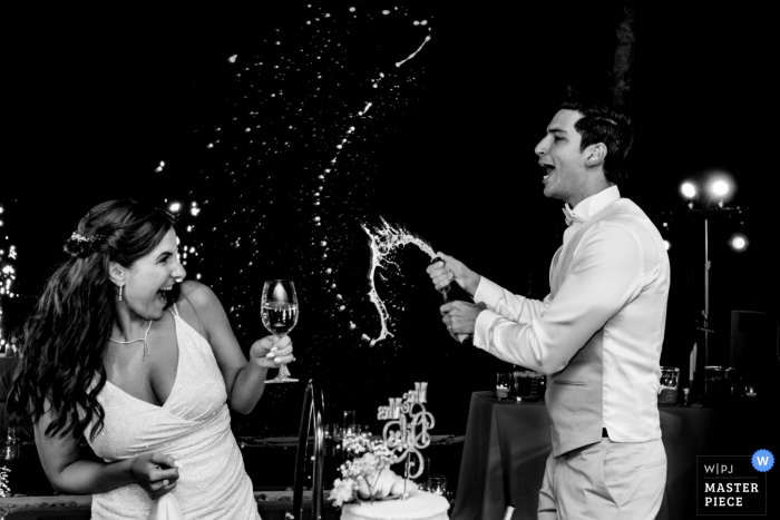 Nikki Beach Dubai wedding photography showing the Splashing of the Champagne on the Bride