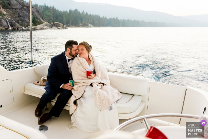 South Lake Tahoe, CA wedding photo showing A bride and groom sharing a quiet moment together on their private boat charter, which they eloped on