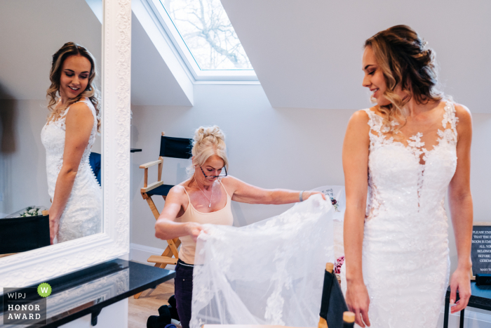West Sussex wedding photography from the Bridal prep suite at Brookfield Barn in Horsham Bride with the reflected mirror as bride's Mum adjusts her dress