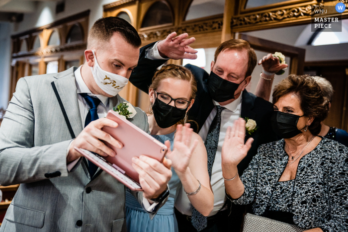 Pennsylvania Ceremony wedding photography showing Sign of the times as the groom gets a livestream set up for the ceremony about to start, his family comes over to say hello to the extended family that couldn't be there in person because of Covid restrict