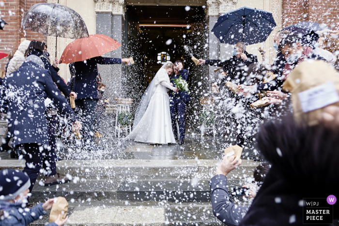 Basilica di San Magno, Legnano, Italy wedding photo showing A storm of rice on the newlyweds